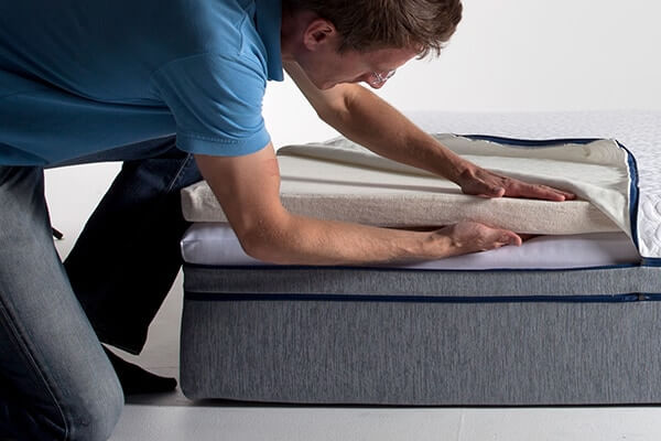 Image of GoodMorning.com founder, Sam Prochazka, carefully inspecting the Comfort+ layer on a Novosbed mattress.