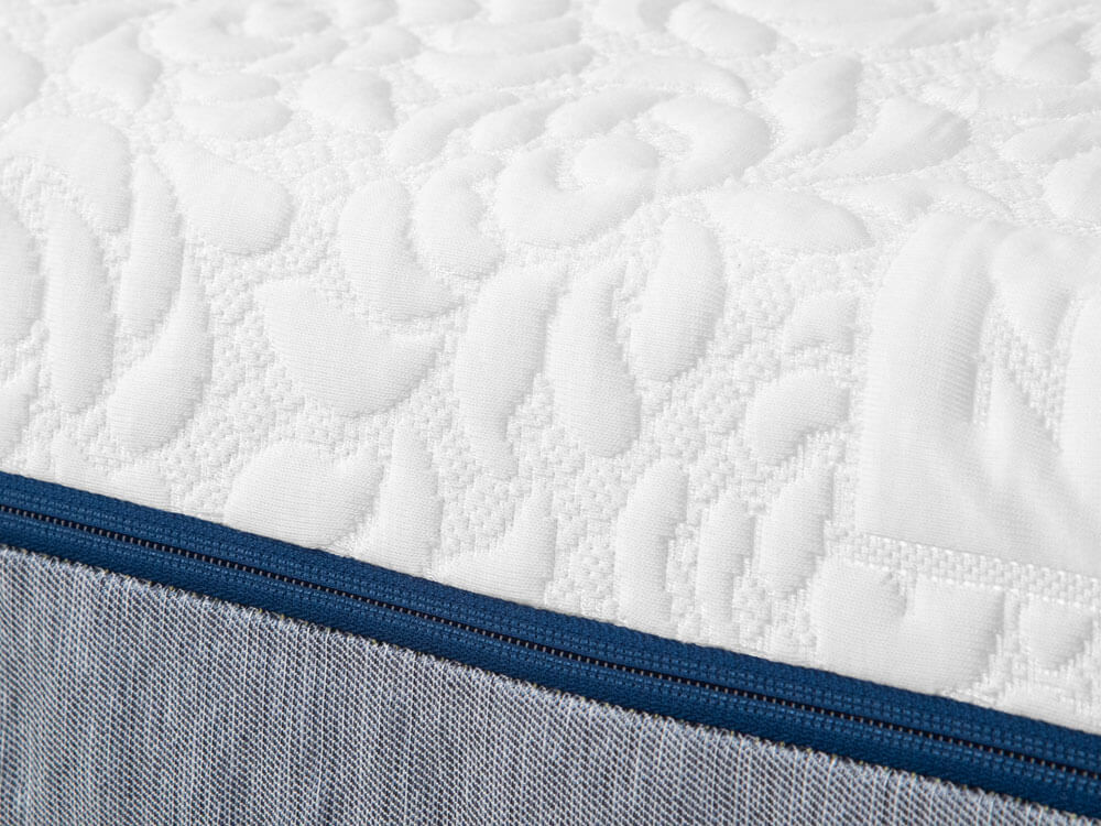 Closeup of the white quilted Tencel cover and blue zipper of the Novosbed premium memory foam mattress